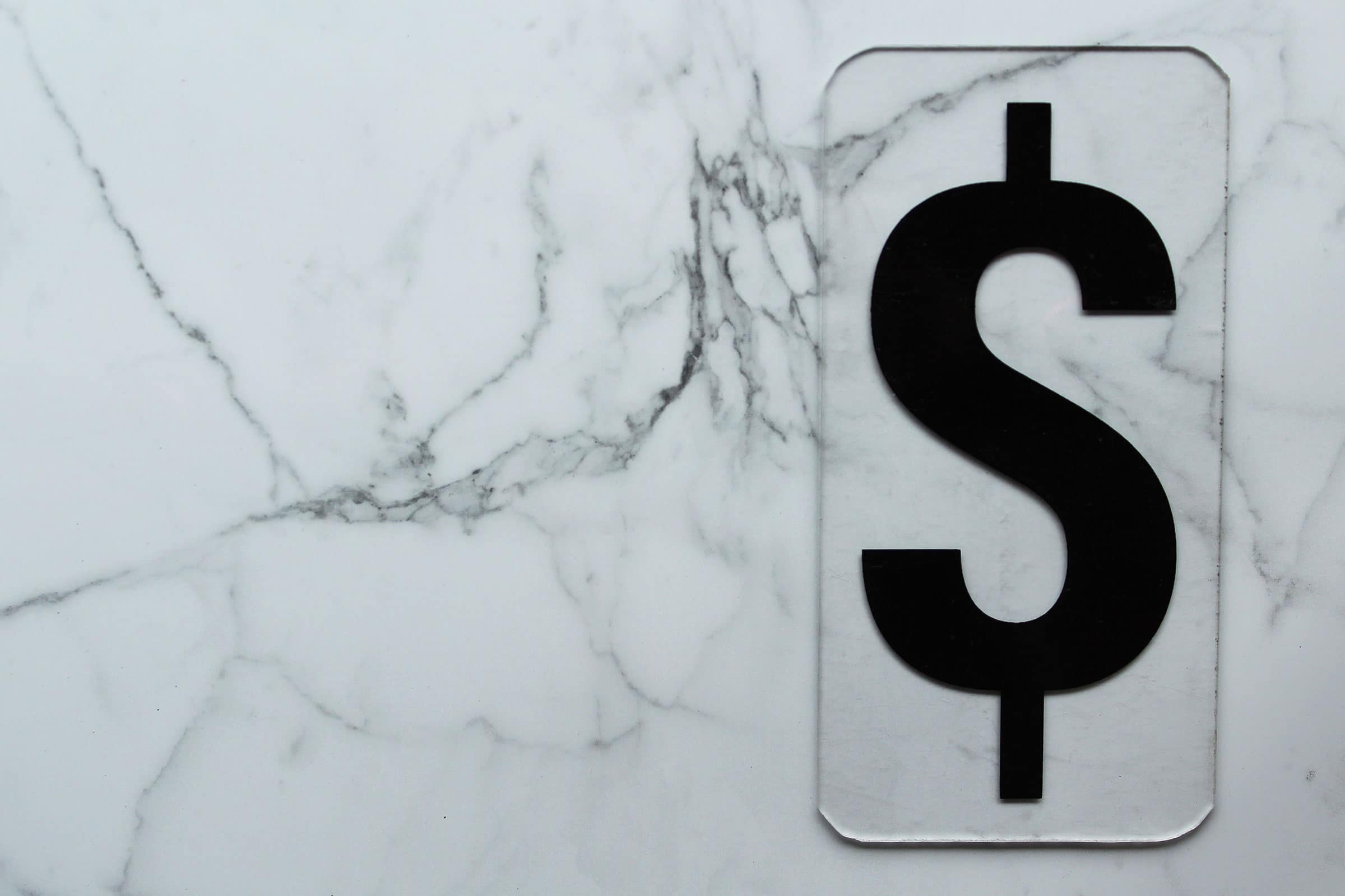 A dollar sign on white marble to communicate how to price your websites as a freelancer