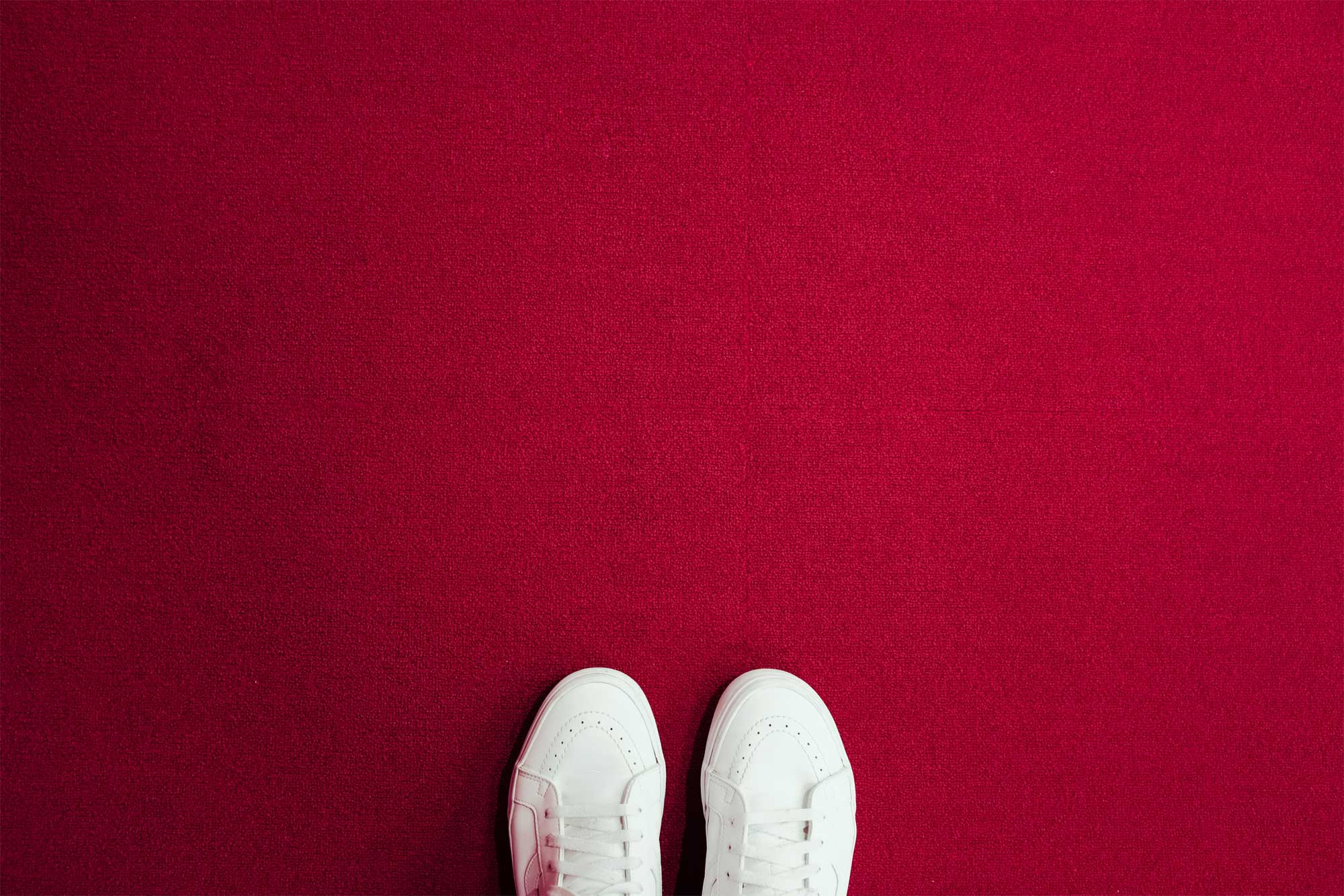 White shoes on a red carpet to suggest starting new freelancing goals